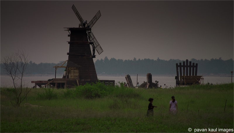 men repairing old windmill by seaside