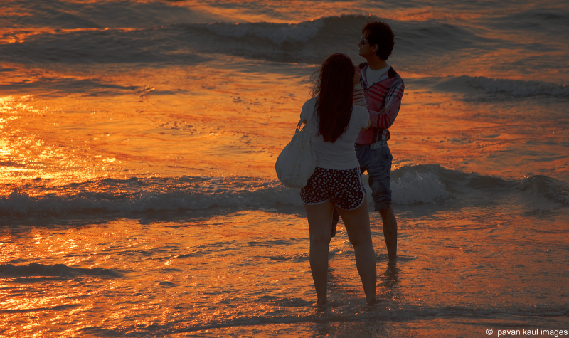 honeymooning couple on beach at sunset