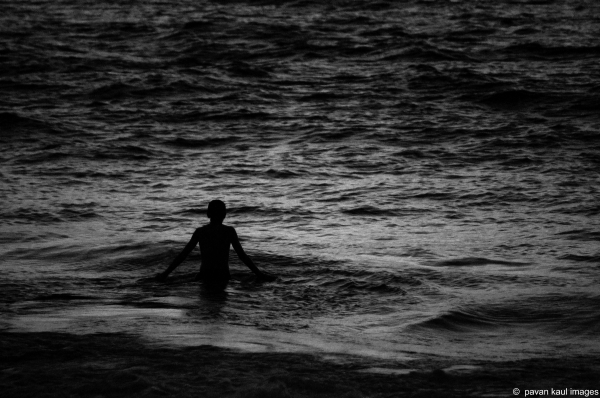 man bathing in ocean at twilight