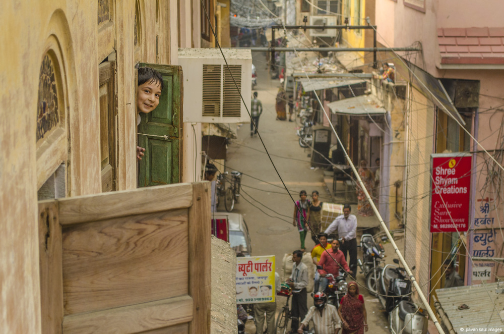 boy smiling out of window in a street in jaipur