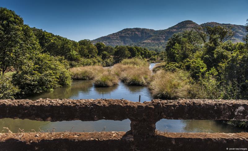 old bridge across stream running through hills