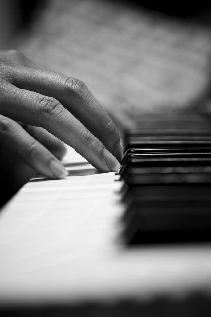 Hand playing piano keys