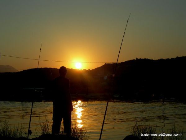 A man fishing in a river in Georgiopouli at sunset