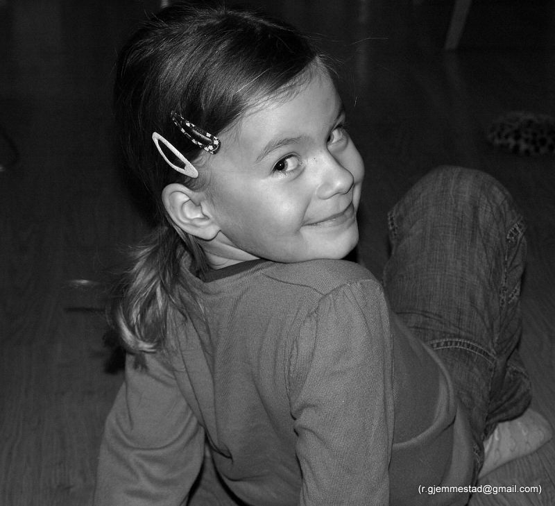 girl smiling over hear shoulder in black and white