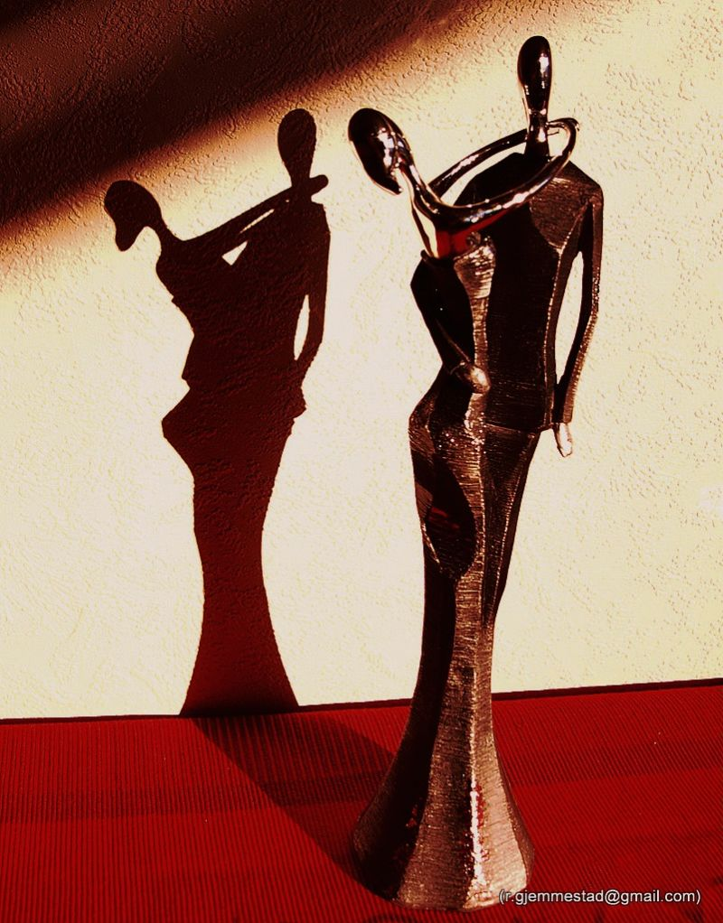 A sculpture of a couple with their shadow
