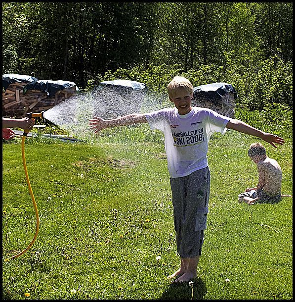 A young boy enjoying a cold shower in the summer