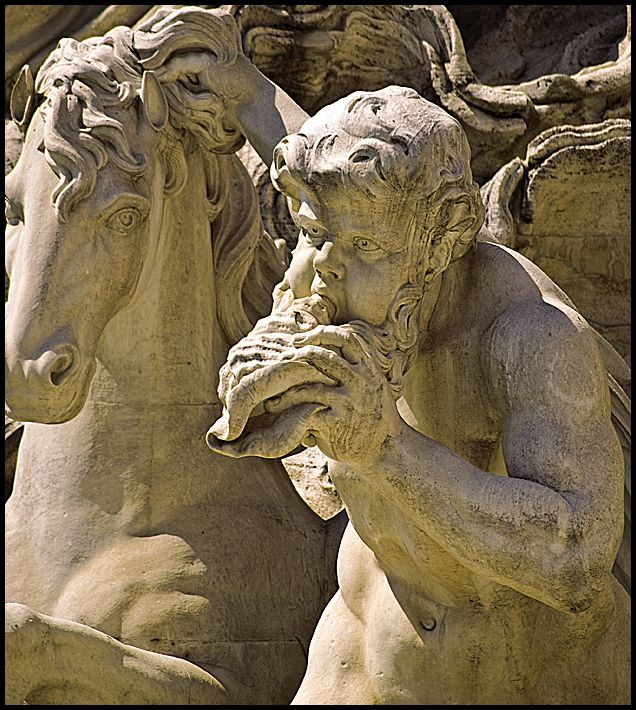 A closeup of a figure in the trevi fountain