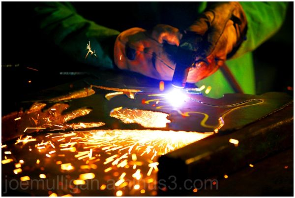metal sculptor working with plasma cutter
