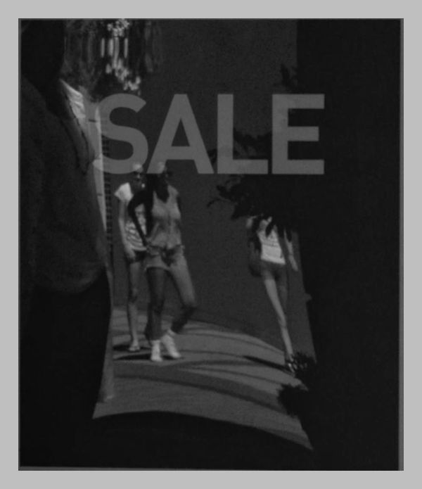 SALE : Passers-by reflected in outside store sign