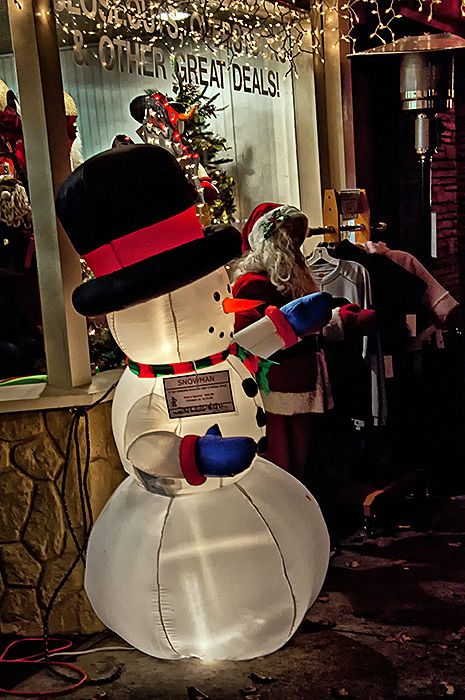 Christmas store lights and snowman at night