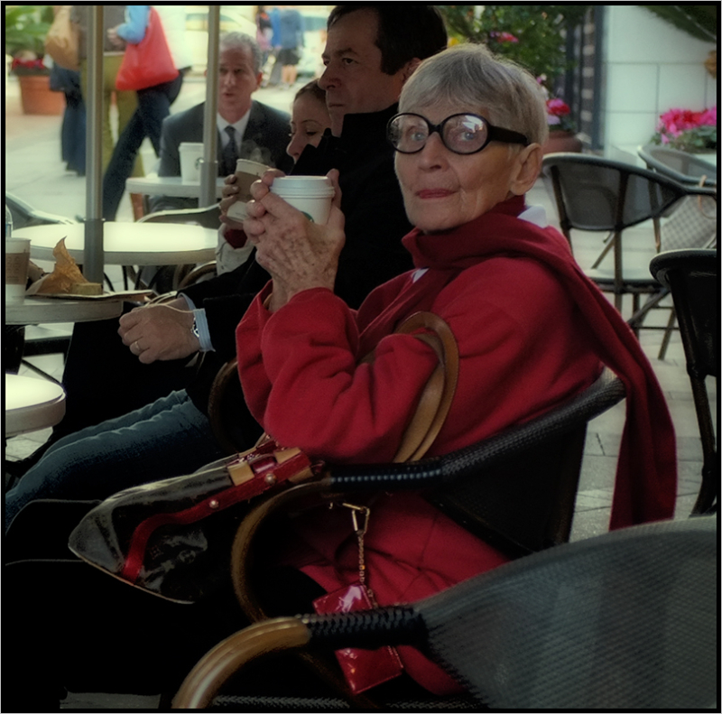 seated woman in red w/round glasses having coffee