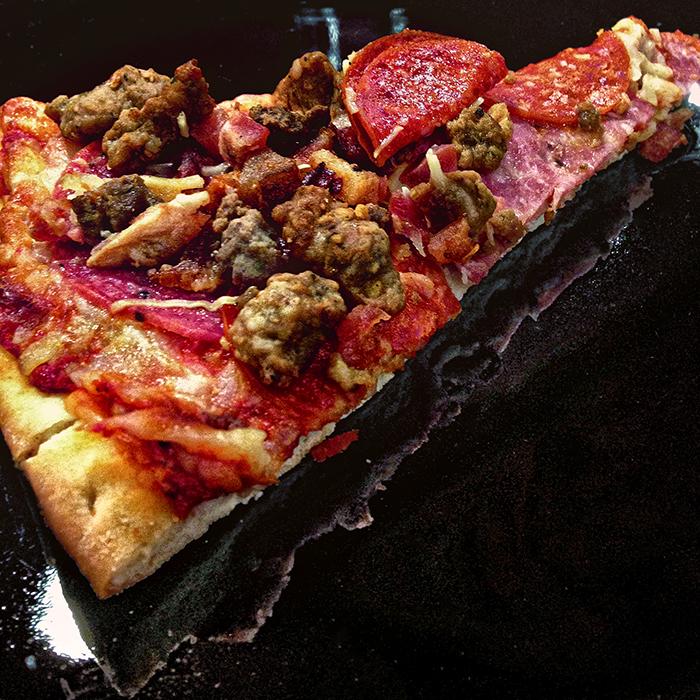 a slice of pizza on a shiny plate