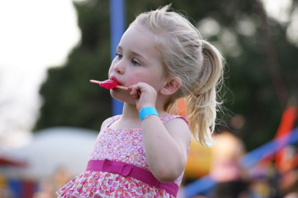 Girl With Popsicle At A Carnival