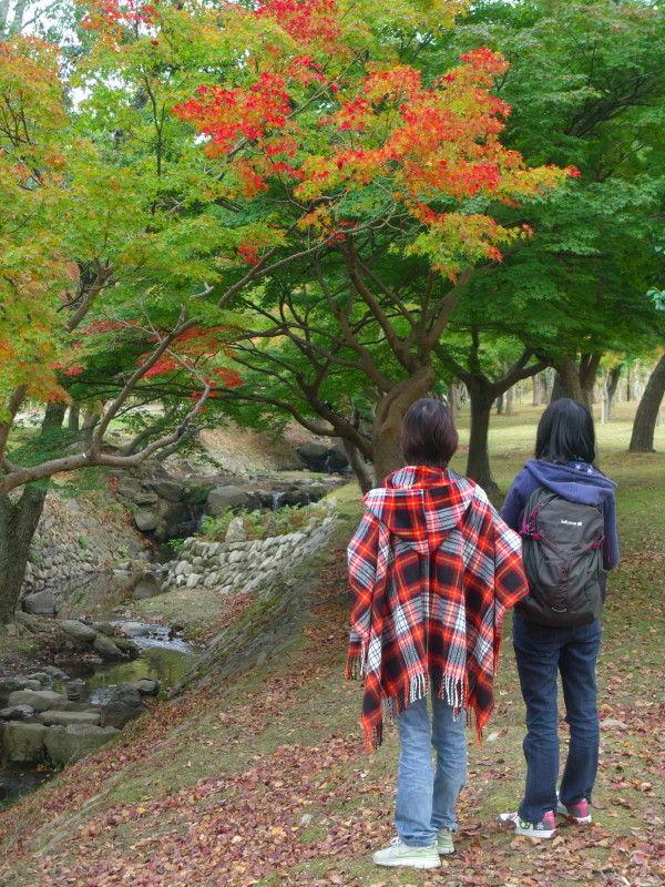 Girls enjoy the beginning of autumn leaves