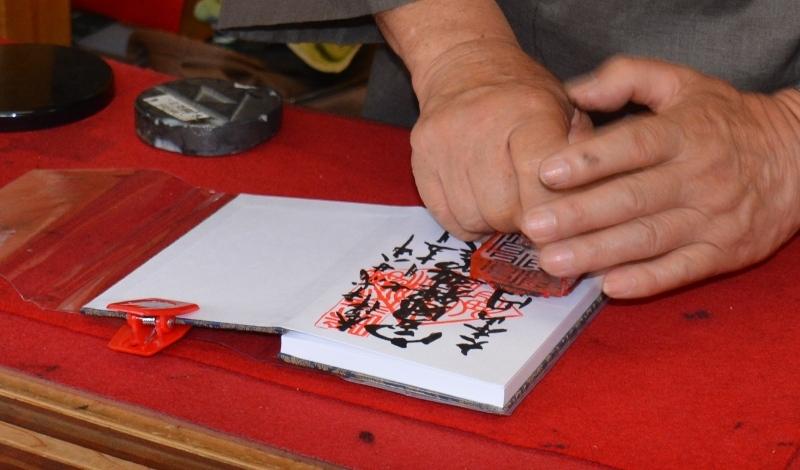 Monjo escrivint al llibre dels visitants als templ