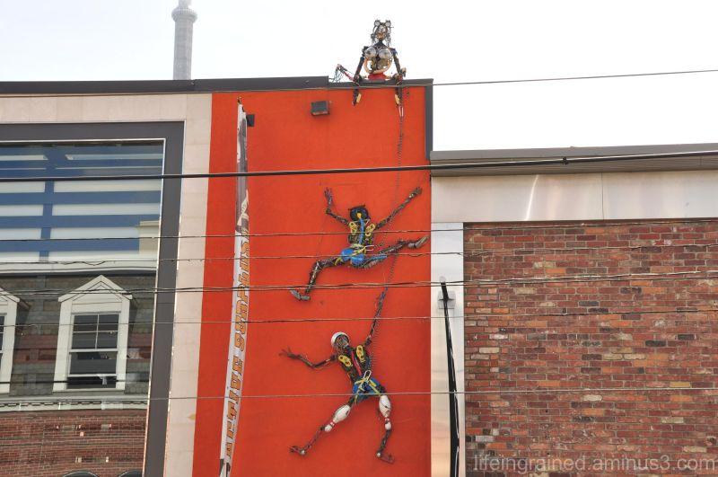 Three women climbing an orange wall...