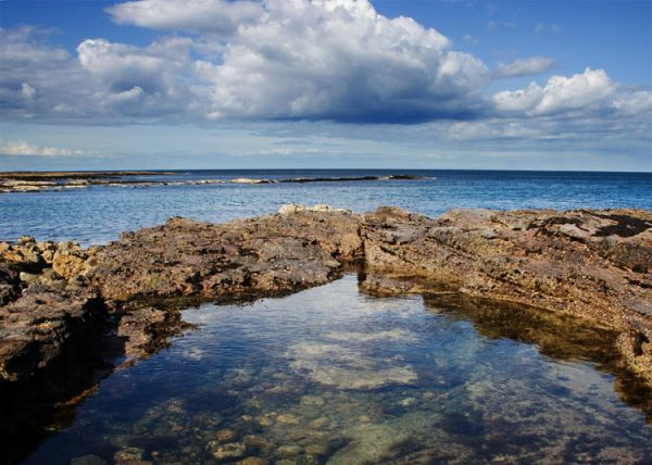rock pools and white fluffy clouds
