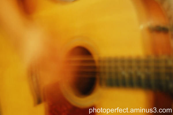 musician playing acoustic guitar, motion blur shot
