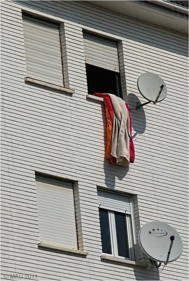 Colcha y edredón colgando de la ventana de un piso