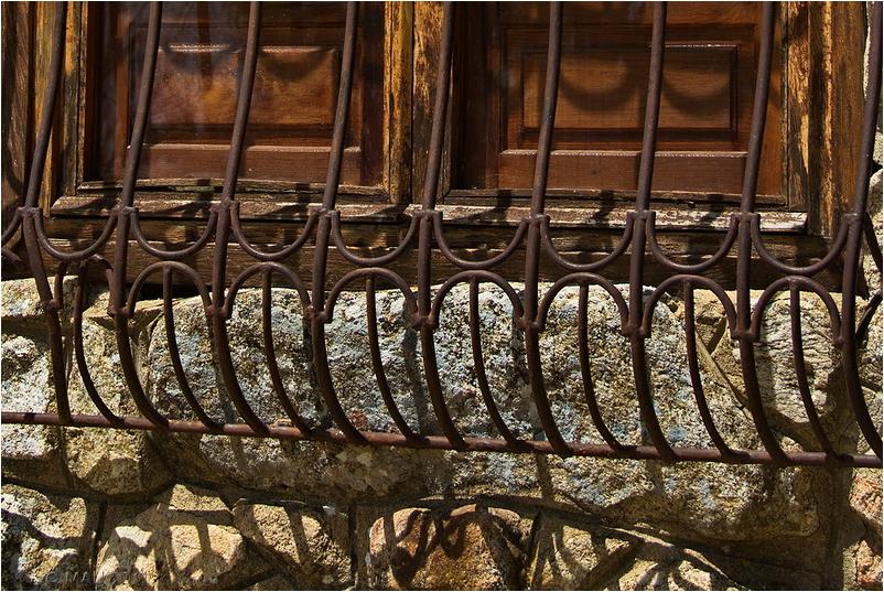 Ventana de madera en un pared de piedra con reja