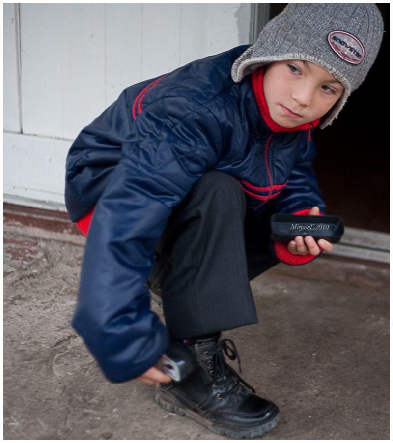 A  boy  brushing  shoes