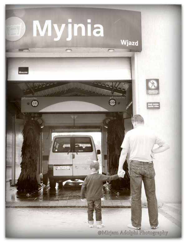 A boy and his father watching carwash
