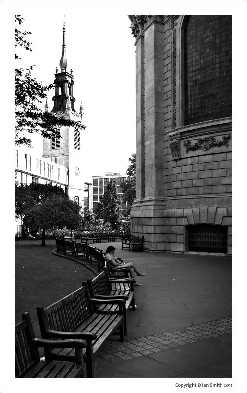 Woman sitting alone in the shadow of St Paul's