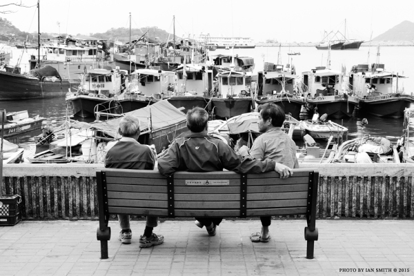 Three men sitting on a bench in Cheung Chau