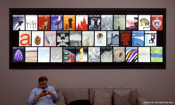 A man sitting below Patek Philippe cover art
