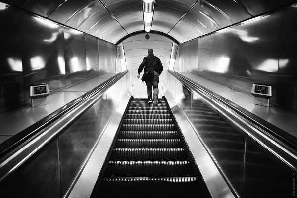 Man walking up escalator on London Underground