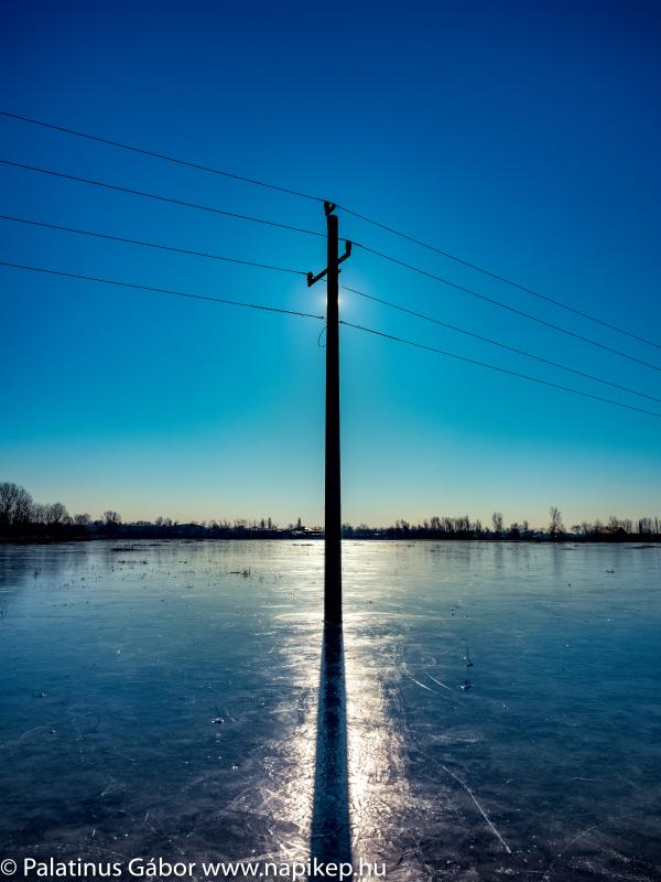 silver bridge on the ice with a pylon