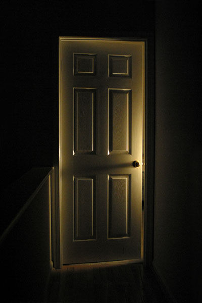 A bedroom door lit by a gentle bedroom light