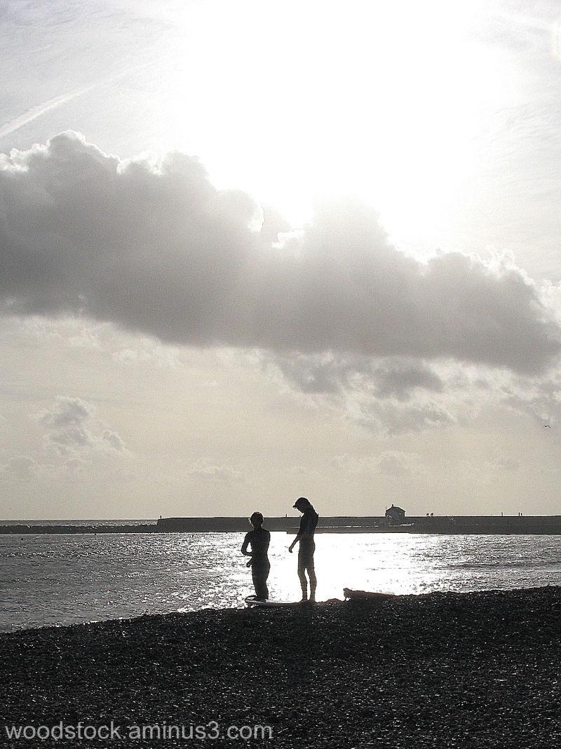 Surfers on the beach at Lyme Regis Dorset