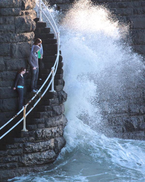 waves pier splash teenagers