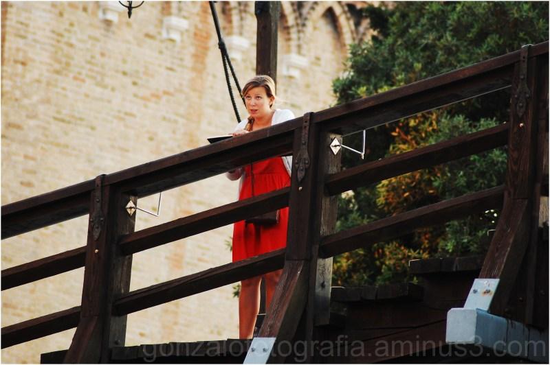Artist with red garment on bridge.