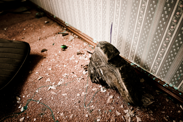 an old boot on the floor of an abandoned house