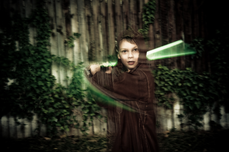 boy in jedi costume with lightsaber