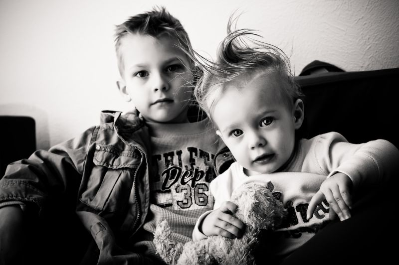 B&W image of a brother and sister in a chair.