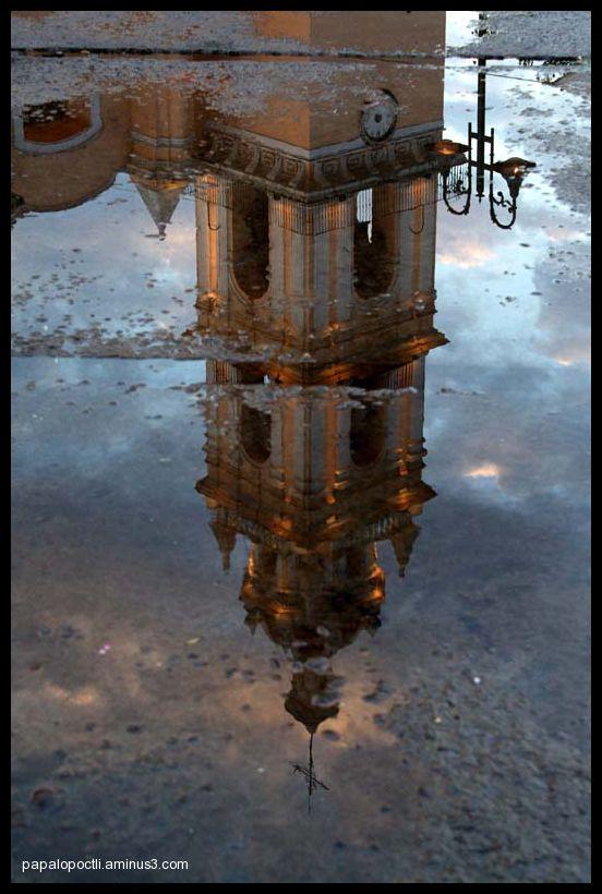 Reflejo de una torre de iglesia en un charco