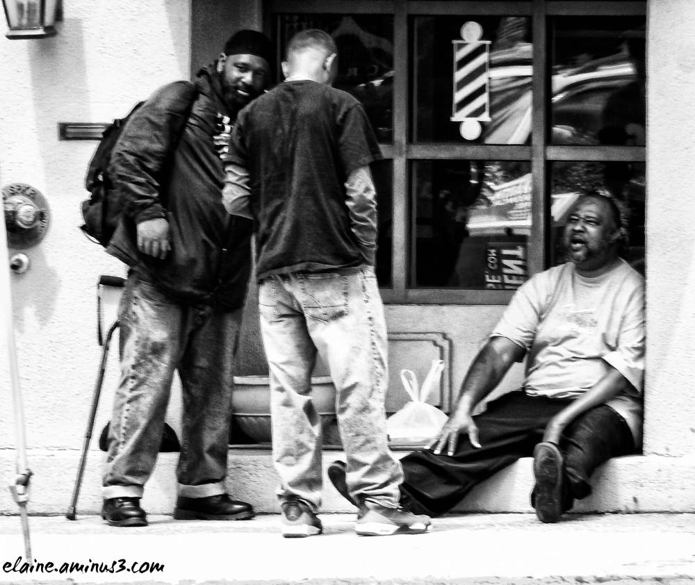 men in front of a barber shop