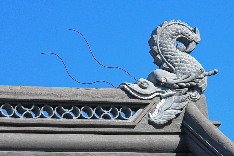 Chinese Garden roof detail of dragon in blue sky