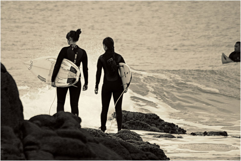 Girls, surfers, waves, rocks