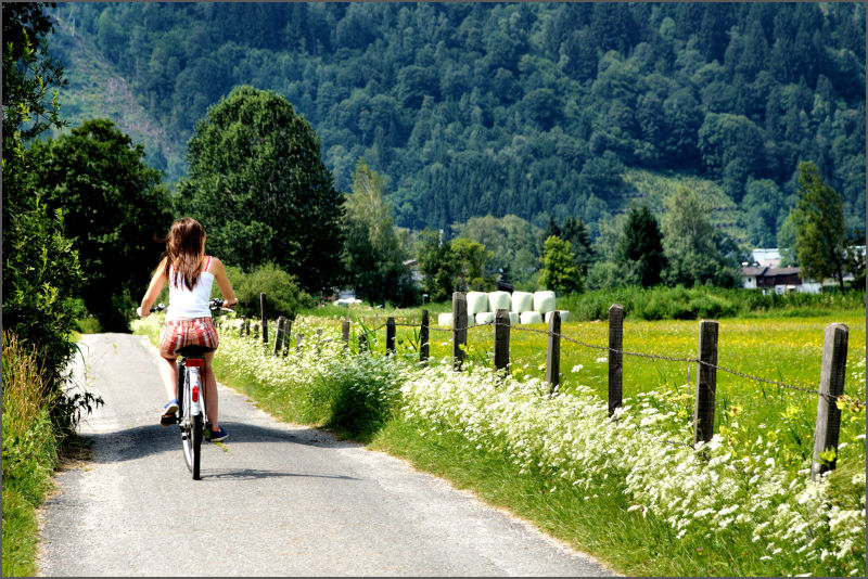 Photograph of a girl cycling along a country lane