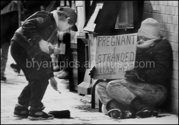 Young boy gives homeless woman xmas money.