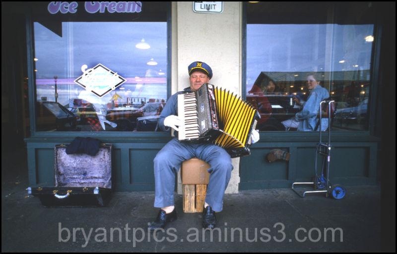 Man playing accordian on sidewalk