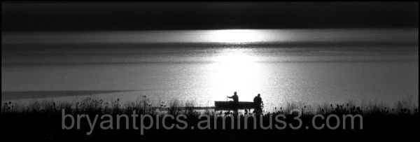 Fishermen in boat on lake as sunsets