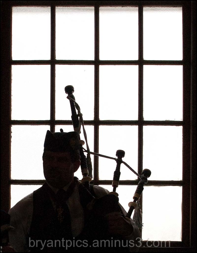Bagpiper back lit in window