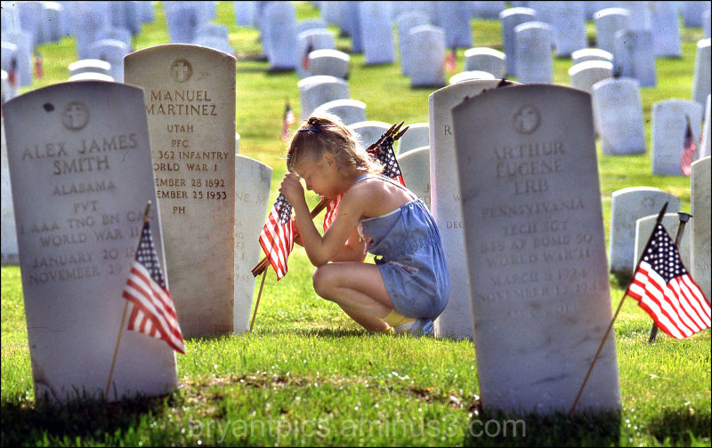 Young girl places US flags on veterans grave
