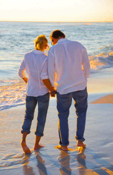 holding hands at sunset on the beach with waves
