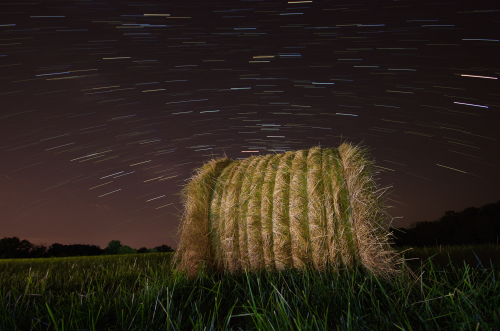 star trails at night on a farm wit hay bail